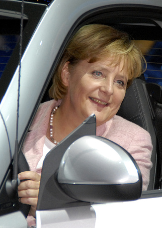 Angela Merkel sits in a Smart hybrid car during the 62th International Auto Show in Frankfurt in 2007