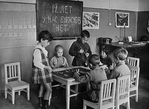 Children in a kindergarten drawing a poster to celebrate the 12th anniversary of the October revolution, 1929