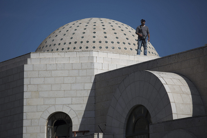 Photo: Police stand and guard on a roof of the synagogue involved in a fatal attack in a religious area of Jerusalem, 18 November 2014