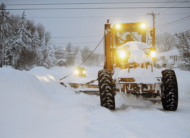 Photo: A New York State Snowgrader moves snow on Broadway in Lancaster, N.Y.