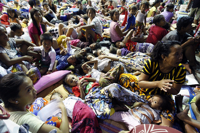 Photo: People take shelter inside a temporary evacuation center in a village of Cebu province, central Philippines, 05 December 2014