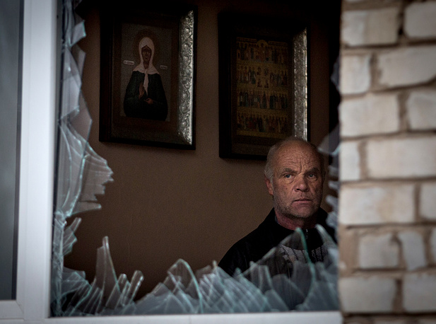 A man looks out of a broken window of a hospital in the town of Pervomaisk, the Lugansk Region