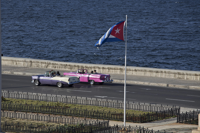 US announced plans to ease restrictions on travel to Cuba, including for family visits, official government business and educational activities. Photo: Tourists ride in a classic American car on the Malecon in Havana, Cuba