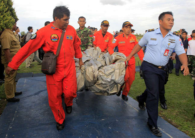 Photo: Members of an Indonesian Air Force crew carry what is believed to be an emergency slide from the AirAsia plane