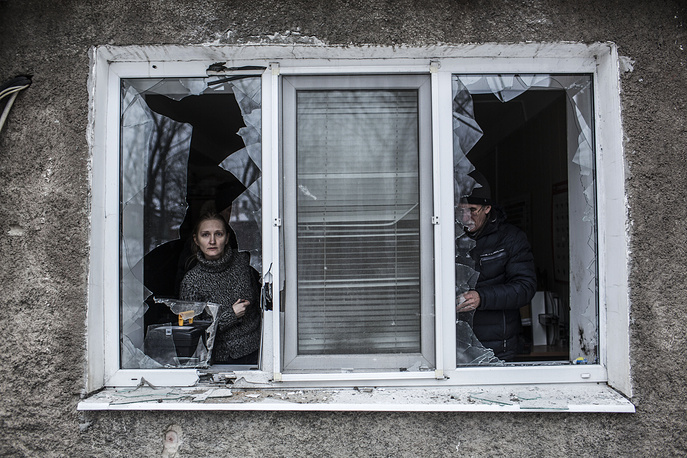 Photo: A Ukrainian woman looks through a broken window at their flat after it was hit by Ukrainian artillery in Donetsk