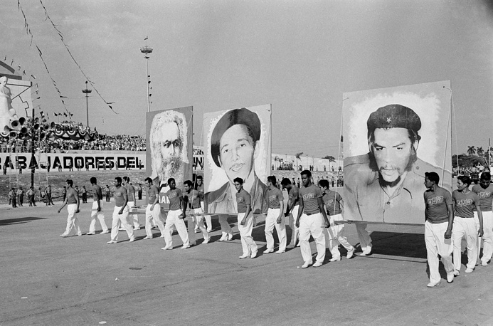 """On April 16 Fidel Castro officially declared the socialist nature of Cuban Revolution. Photo: Cuban athletes carrying portraits of Karl Marx, Raul Castro, and Ernest """"Che"""" Guevara, during May Day parade in Havana, May 1, 1961"""