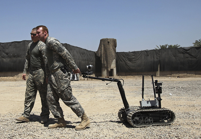 US soldiers pull a robot used for explosives disposal in Baghdad, Iraq