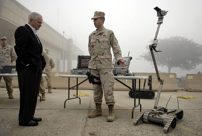 US Defense Secretary Robert Gates speaking with US Air Force Senior Airman about the capabilities of their robots at Camp Victory in Baghdad, Iraq