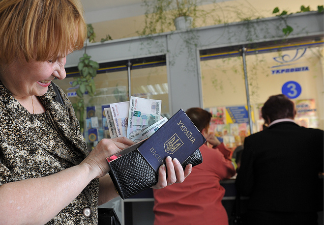Crimean pensioners started to get their pensions, recalculated in accordance with Russian law. Photo: A woman has got her pension in rubles at a post office in Simferopol