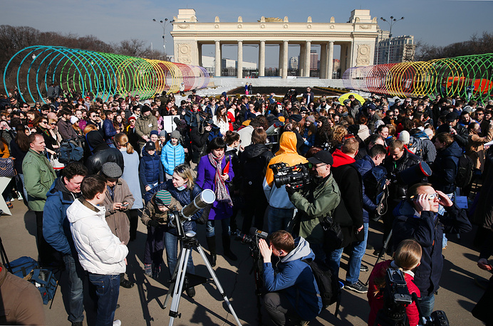 People gathering in Moscow's Gorky Park to watch a partial solar eclipse