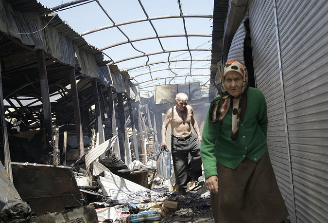 The ceasefire between the Ukrainian conflicting sides agreed on February 12, 2015 in Minsk has been repeatedly violated. Photo: Local residents passing damaged shops after shelling at a market in Oktiabrskiy district near the International Airport in Donetsk, Ukraine, 07 June 2015