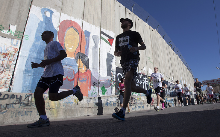 Palestinians and foreigners running past the separation barrier during the second annual Palestine International Marathon in the West Bank town of Bethlehem