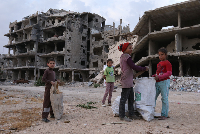 Children collecting timber in a street in the Dahaniya neighborhood of Damascus
