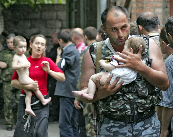 Beslan school siege which started on 1 September 2004, lasted three days and ended with the death of 335 people. Photo: A soldier with a baby and a woman following him after the release of 26 women with their children in Beslan, North Ossetia, 02 September 2004