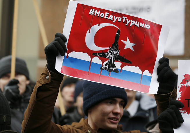 A Russian protester holding a placard reading: 'Don't go to Turkey', as he takes part in a rally in front of Turkish embassy in Moscow, Russia