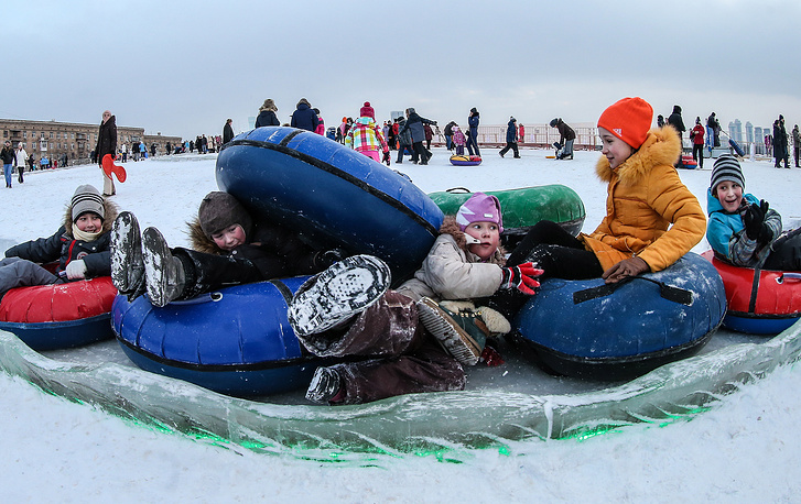 Kids sliding down a tubing slope on Moscow's Poklonnaya Hill.