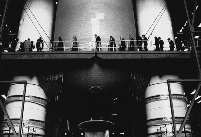 Members of the Presidential Commission on the Space Shuttle Challenger Accident walking past the solid rocket boosters and the external tank of a shuttle