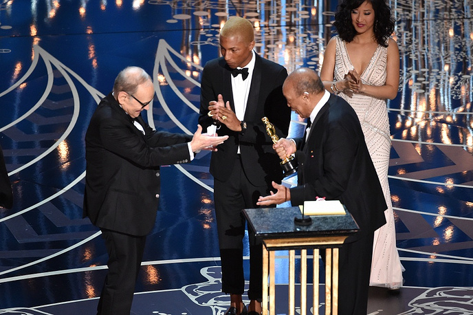 Composer Ennio Morricone accepting the Best Original Score award for ''The Hateful Eight' from musicians Pharrell Williams and Quincy Jones