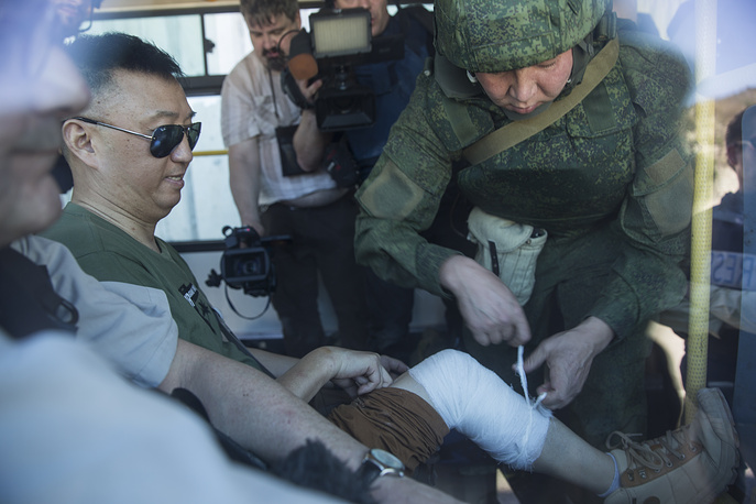 A Chinese reporter is bandaged by Russian military officer