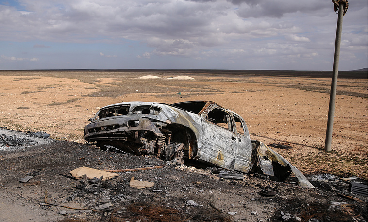 A burnt out car wreckage on a road to Aleppo