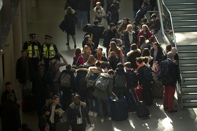 A group of travelers stand together, after services were suspended on the Brussels Eurostar train route because of the attacks in Belgium, in London