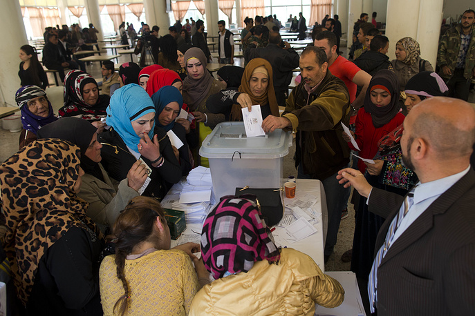 Syrian woman casts her vote at a polling station during the Syrian parliamentary election in Damascus