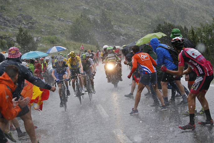 Ireland's Daniel Martin, Britain's Chris Froome, wearing the overall leader's yellow jersey, Colombia's Nairo Quintana, and Britain's Adam Yates, wearing the best young rider's white jersey, climbing in pouring rain towards Andorra Arcalis