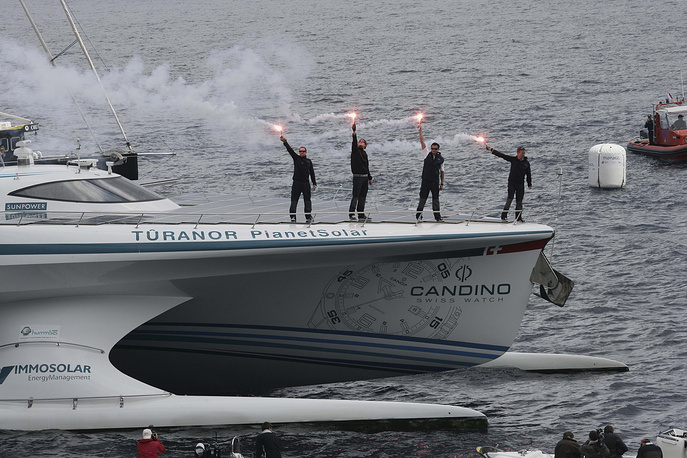 The sailors of the MS Turanor PlanetSolar, the world's largest solar boat ever built, standing on the deck with flares after they have achieved the first around-the-world journey using solar energy in 585 days, off the Monaco's harbour, France. The five sailors are : Raphael Domjan of Switzerland, founder and expedition leader, Patrick Marchesseau of France, Erwann le Rouzic of France, Jens Langwasser of Germany and Christian Oechsenbeim of Switzerland