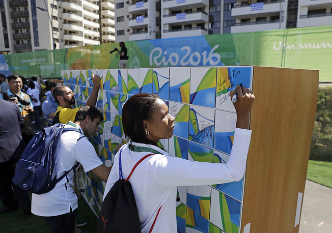 Athletes, officials and volunteers signing a mural in the athletes village in Rio de Janeiro