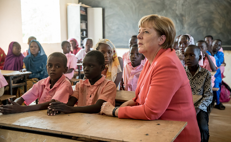 German Chancellor Angela Merkel speaks with primary school students from the Goudell II. school in Niamey, Niger, October 10