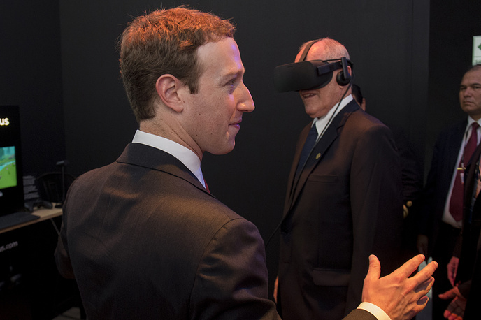 Founder and CEO of Facebook Mark Zuckerberg  observes Peruvian President Pedro Pablo Kuczynski who tries a virtual reality artifact at the stand of Facebook at APEC summit in Lima