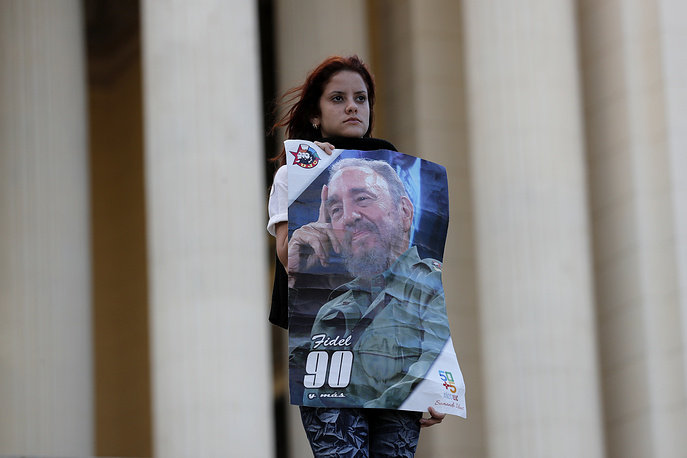 A student stands holding images of Fidel Castro at the university where Castro studied law as a young man, during a vigil in Havana, November 27