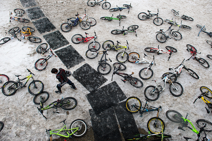Bikes lying on the ground ahead of in a mass downhill mountain biking event on alpine ski tracks on Mount Aibga, at the Gorky Gorod ski resort, Sochi, May 7