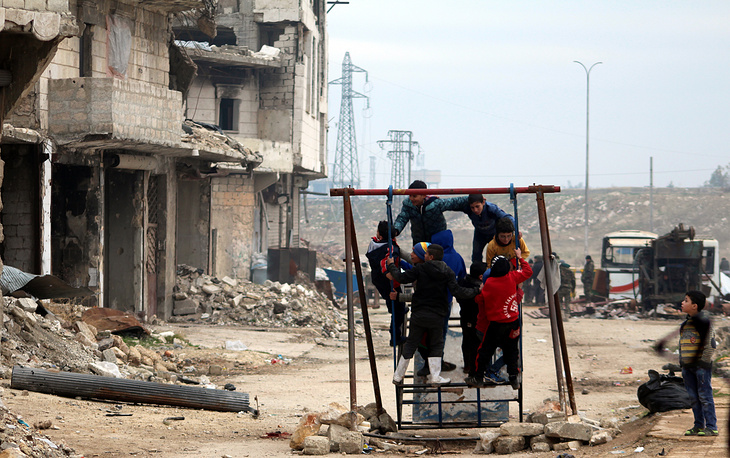 Children play near a damaged building in Salah al-Din area, in eastern Aleppo