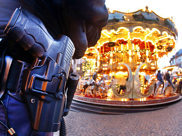 A German police officer stands next to a merry-go-round in the Christmas market in Frankfurt, Germany, December 20