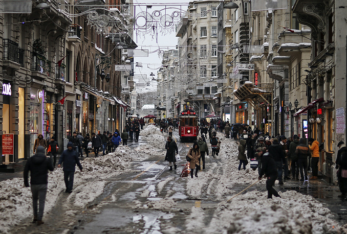 People walk through the slush in Istiklal Avenue, the city's main shopping road, in Istanbul, January 10