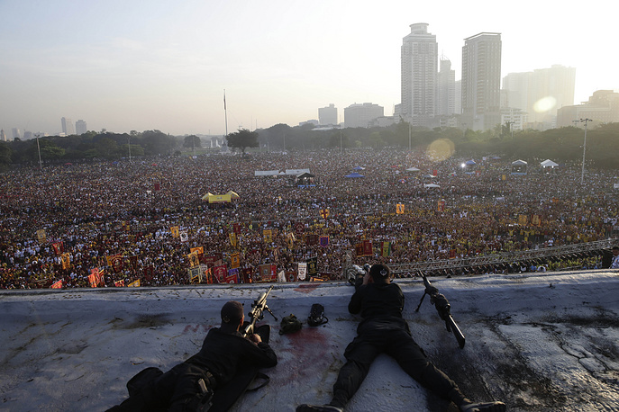 Police snipers watch at thousands of devotees who gathered at Manila's Rizal Park to celebrate the feast day of the Black Nazarene, Philippines, January 9