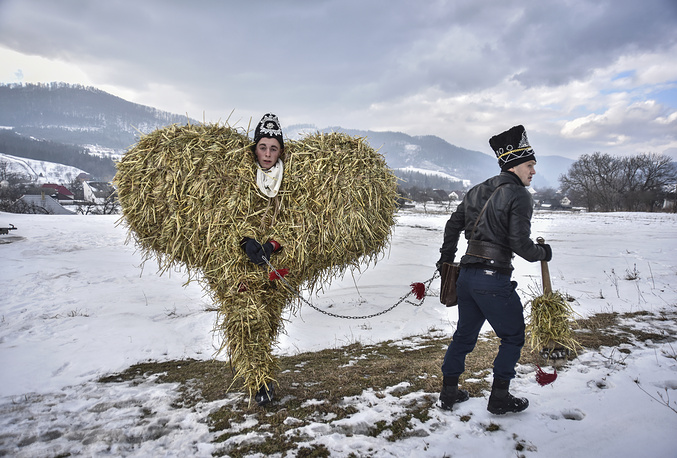 A man in a bear costume, made of hay and reed, pulled by another man dressed as a gypsy as they march during the celebrations of the winter holiday 'Malanka', or 'Old New Year Celebrations' in the village of Krasnoilsk, Ukraine, January 14