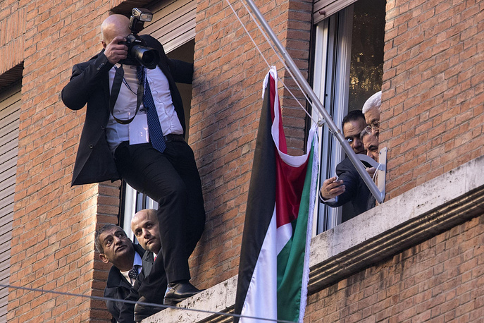 Photographer leans out of a window to take pictures of Palestinian President Mahmoud Abbas inaugurating the new Palestinian Embassy at the Vatican, after a private audience with Pope Francis, January 14