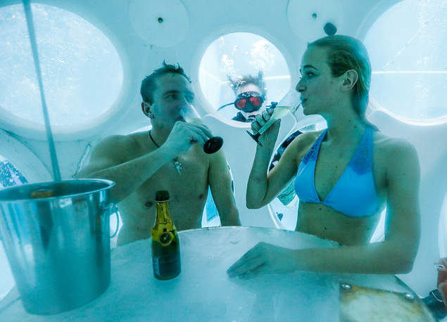 "People drink champagne while sitting inside ""The Pearl"", a spheric dining room placed 5 metres underwater in the NEMO33 diving center, one of the world's deepest pools (33 metre) built to train professional divers, in Brussels, Belgium, January 31"