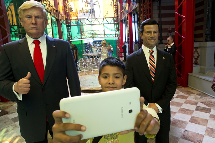 A boy takes a selfie between wax replicas of US President Donald Trump and Mexico's President Enrique Pena Nieto, at the Wax Museum in Mexico City, February 1