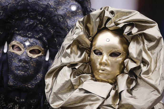 Masked women's stand in San Mark's square during the Venice Carnival, in Italy