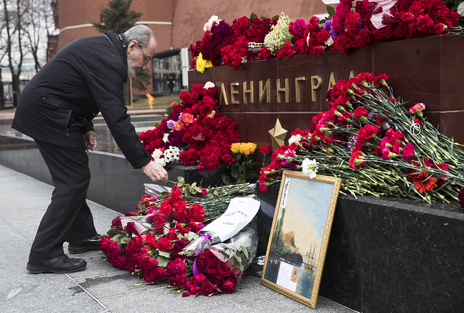 A man lays flowers in memory of victims killed by a bomb blast in a subway train in St. Petersburg, at the Leningrad (St. Petersburg) Hero City memorial in front of the Kremlin wall in Moscow