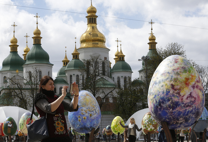 A woman takes pictures of Easter eggs on display in front of St. Sofia Cathedral in Kiev, Ukraine, April 12
