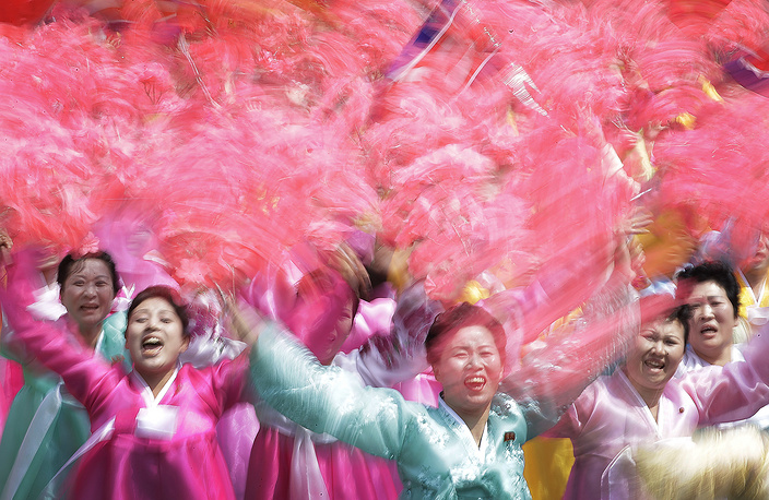 North Korean women wave and cheer as they look toward their leader Kim Jong Un during a military parade in Pyongyang, April 15