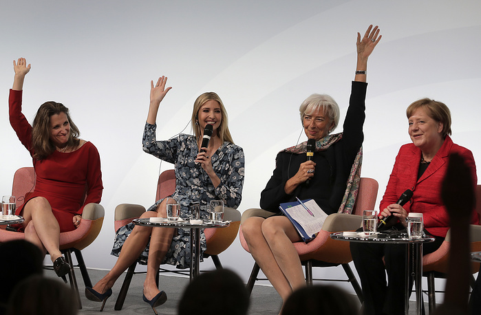 Canada's Foreign Minister Chrystia Freeland, Ivanka Trump and Christine Lagarde jokingly raise their hands to support that they consider German Chancellor Angela Merkel being a feminist during a panel at the W20 Summit in Berlin