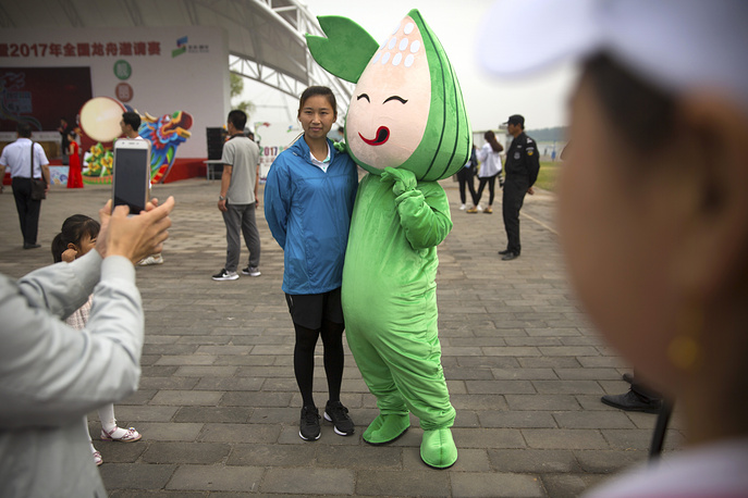 A woman poses for a photo with a character dressed like a zongzi, a traditional Chinese sticky rice dumpling, during the Dragon Boat festival in Beijing