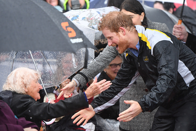 Britain's Prince Harry reacts as he recognises 97-year-old Daphne Dunne, who he had met on an earlier visit to Sydney, during a walk around as it rains at The Rocks in Sydney, Australia, June 7