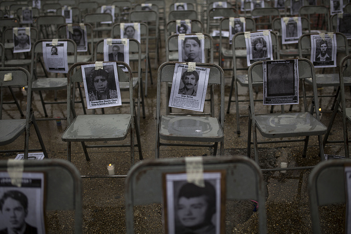 """Chairs bearing portraits of people who were disappeared during the 1980's, sit empty in a ceremony marking the National Day of the Disappeared in Guatemala City, June 21. According to human rights groups, more than 40,000 people were """"disappeared"""" during Guatemala's 36 years of internal conflict"""