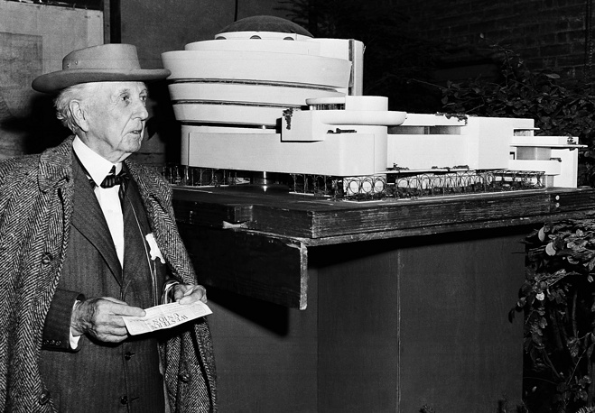 Architect Frank Lloyd Wright next to a model of the new building he designed for the Solomon R. Guggenheim Museum in New York, 1953